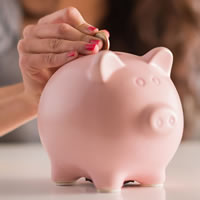 Person putting coin into a pink piggy bank.