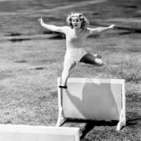 Vintage photo of young woman hurdling over an obstacle.